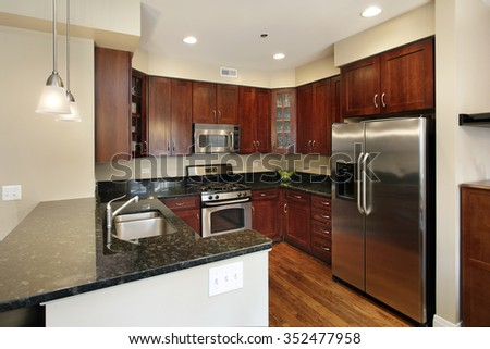 Kitchen in condominium with cherry wood cabinetry #352477958