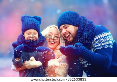 portrait of happy family blowing winter snow outdoors, holiday season