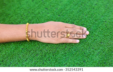 a ladies hand with gold bracelet and gold ring at green grass background #352543391