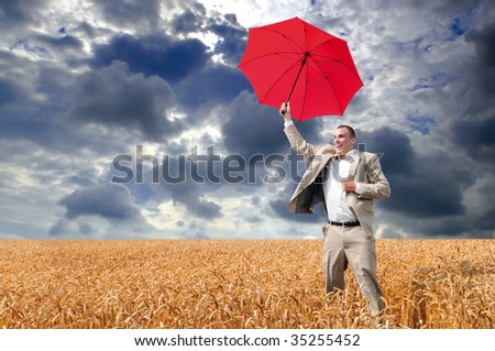 Businessman with red umbrella jumping in a field of wheat with dark cloud background #35255452