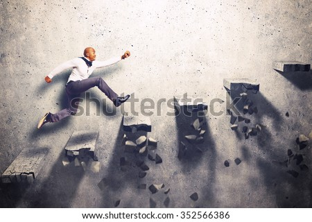 Man climbs the steps of collapsing ladder Royalty-Free Stock Photo #352566386