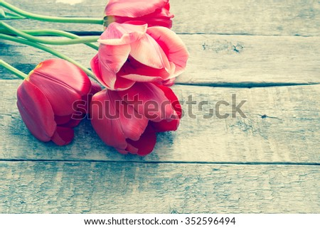 Red tulips on a wooden surface/toned photo #352596494