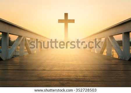 silhouette christian cross at railhead wooden bridge and orange sky with lighting,religion concept