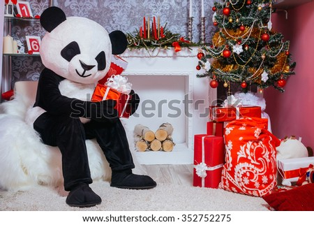Preparing for Christmas. Fairy tale character in costume of panda sitting in the interior of the Christmas room and holding a present