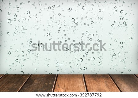 Wooden floor platform with rainy drops water on glass background. #352787792