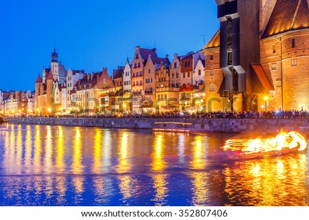 Multi-colored facades and boat on the central waterfront in Gdansk at night. #352807406