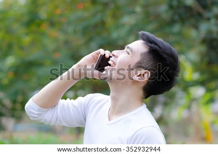 Portrait of a smiling guy talking on mobile phone outside, Asian man talking on mobile. #352932944