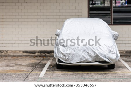Silver cover for new car which parked in the outdoor ground. Royalty-Free Stock Photo #353048657