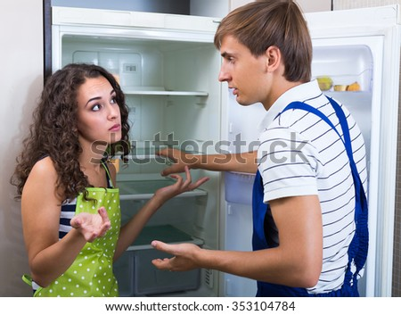 Tired handyman cannot repair refrigerator at the kitchen of female client  #353104784
