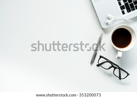 Desk with laptop, eye glasses, earphone, pen and a cup of coffee. Top view with copy space. Royalty-Free Stock Photo #353200073