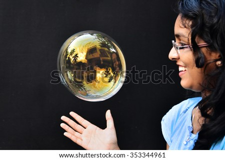 A happy Indian teenage girl trying to catch a large colorful soap bubble against black background. #353344961