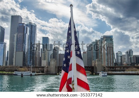 An American flag waves on the back of a ferry boat looking towards the downtown skyline of Chicago