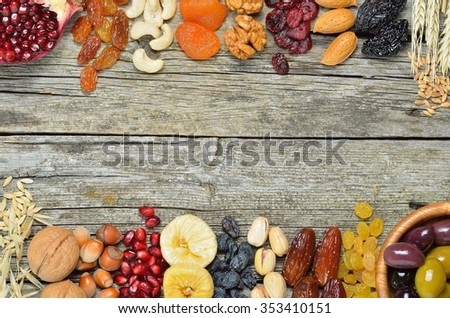 Mix of dried fruits and nuts, barley, wheat, olives, pomegranate on wooden table  - symbols of judaic holiday Tu Bishvat. Copyspace background.Top view. #353410151