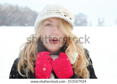 winter woman in snow photo, looking and blows breath at camera outside on cold winter day. Portrait Caucasian female model with pink gloves and white hat with scarf in first snow