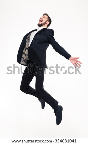 Excited elated happy young business man with beard in classic suit jumping and shouting over white background #354081041