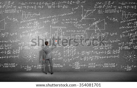 Rear view of man drawing formulas on blackboard with chalk #354081701