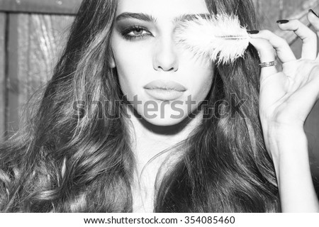 One pretty tender dreaming young fashionable woman with long curly hair bright makeup and white fluffy feather from angel wing near face in black cloth dress on wooden background, horizontal picture