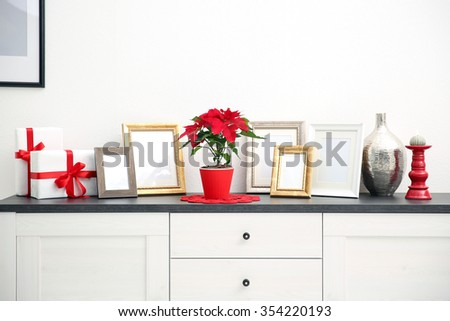 Christmas flower poinsettia and decorations on drawers with Christmas decorations, on light background