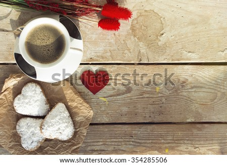 Heart shaped cookies (powdered sugar), cup of coffee, decoration red heart on old wooden table. sunny morning. Christmas breakfast or Valentine's Day Breakfast. Toned image