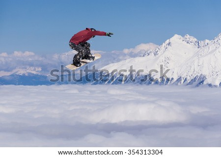 Flying snowboarder on mountains. Extreme winter sport. #354313304
