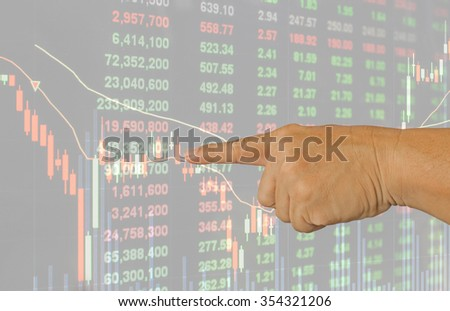 hand of a man pointing at stock price graph