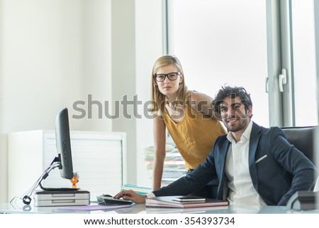 Portrait of business partner sitting at his tidy glass desk in front of his computer in a luminous white office with his blonde female associate standing behind him. They are looking at camera #354393734