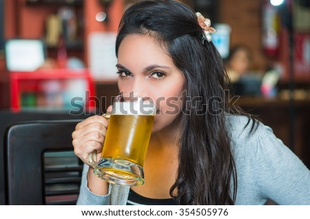 Brunette model sitting by restaurant table drinking from glass of beer and posing with positive attitude smiling. #354505976