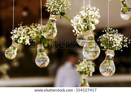 Original wedding floral decoration in the form of mini-vases and bouquets of flowers hanging from the ceiling Royalty-Free Stock Photo #354527417