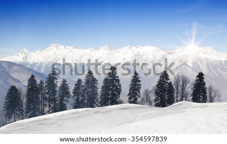 Ski-track with Caucasus mountains on background. Ski vacation panorama on top of the mountain. No people. Winter, snow and sunshine. #354597839