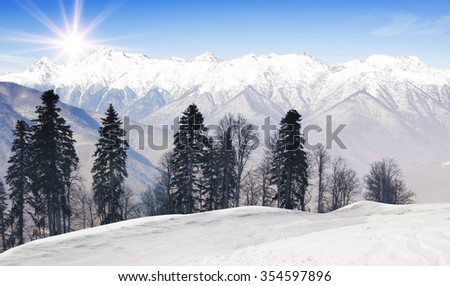 Ski-track with Caucasus mountains on background. Ski vacation panorama on top of the mountain. No people. Winter, snow and sunshine. #354597896