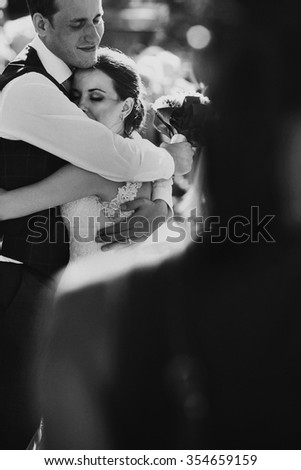 Beautiful bride and groom embracing and kissing on their wedding day outdoors #354659159