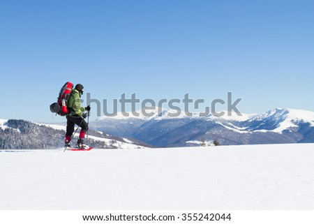 Winter hiking in the mountains on snowshoes with a backpack and tent. #355242044