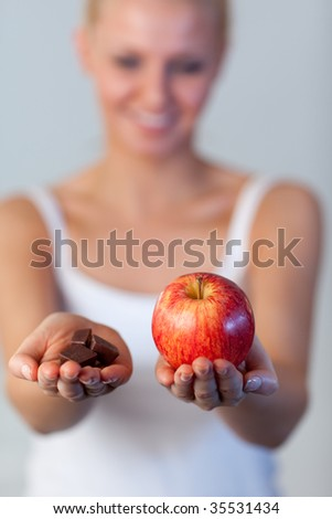 Young beautiful woman holding chocolate and an apple with focus on apple #35531434