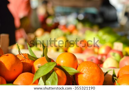 Closeup picture of bright oranges with fresh fruits and vegetables at market in boxes on the background