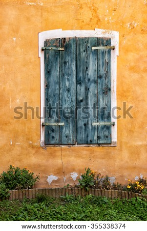 An old wooden window and an yellow wall #355338374