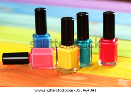 Bottles of nail polish on a colorful wooden table #355464041