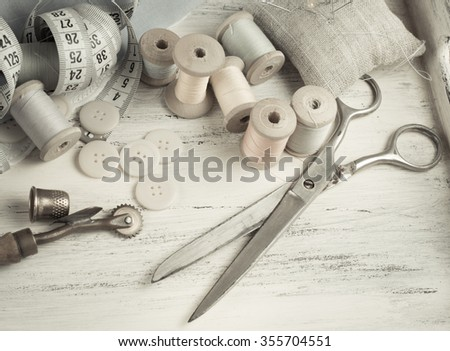 Set of reel of thread, scissors, buttons, fabric and pins for sewing and needlework in Shabby Chic style. For this photo applied toning in retro style. #355704551