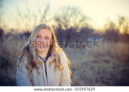 Portrait of a smiling young woman looking at the camera, with blue eyes and blond hair. Shot outdoors in a cold autumn day with natural background. #355947629