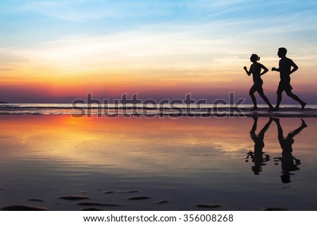 two runners on the beach, silhouette of people jogging at sunset, healthy lifestyle background with copyspace Royalty-Free Stock Photo #356008268