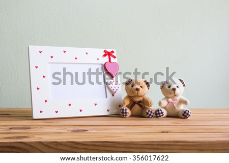 White vintage photo frame with red heart and teddy bear on wooden table over wall grunge background, Valentine day concept.