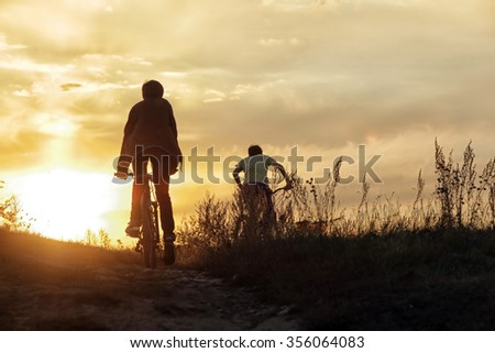 summer landscape silhouette of a boy on a bicycle, with rolling hills on the background of golden sunset  #356064083