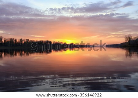 autumn landscape magnificent sunset over the river and reflected clouds in a mirror surface  #356146922