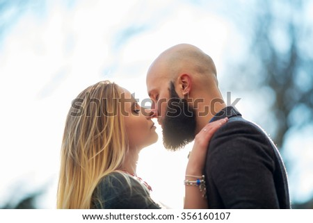 Young outdoor fashion portrait of beautiful couple kissing on the street #356160107