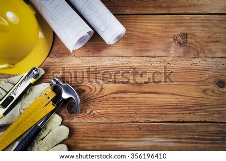 hammer, protective gloves, folding ruler, model knife, blueprint and yellow safety helmet on wooden background #356196410