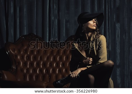 One beautiful serious young stylish fashionable brunette woman in autumn beige coat and round black hat sitting on leather couch indoor looking away copy space, horizontal picture