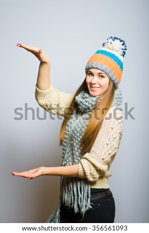 Happy beautiful girl shows a rising trend, knit cap, winter concept, photo studio, portrait of a woman isolated on gray background