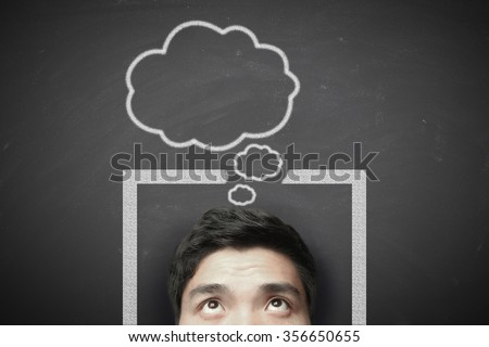 Man thinking outside the box with blackboard background.