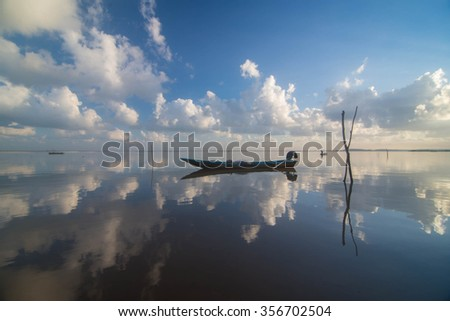 reflection of sky and boat during sunrise Royalty-Free Stock Photo #356702504