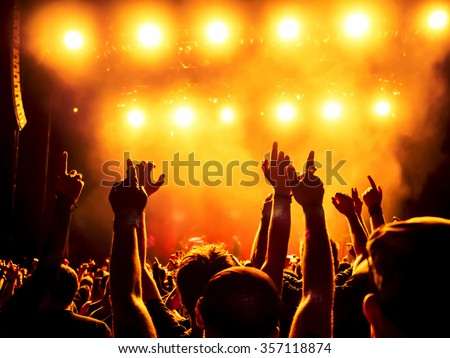 silhouettes of concert crowd in front of bright stage lights #357118874