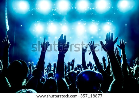 silhouettes of concert crowd in front of bright stage lights #357118877